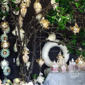 Decorazioni per l'albero di Natale a tema mare: conchiglie, meduse, stelle marine bianche e dorate.