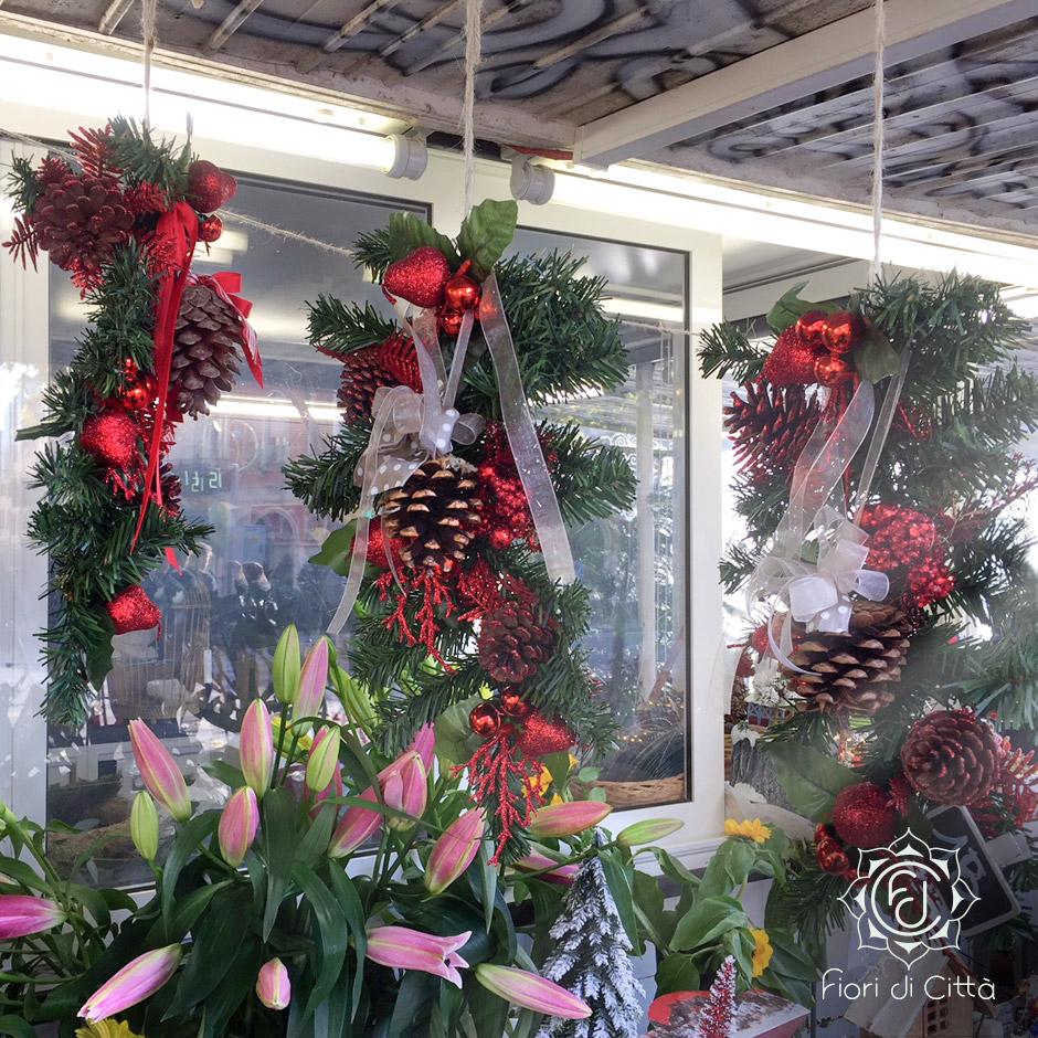 un ramo di pino decorato con pigne e natri rossi