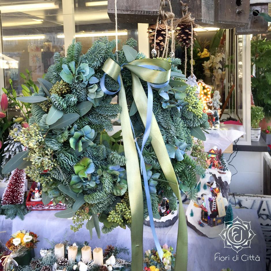 Ghirlanda natalizia con rami di pino e fiori, perfetta anche quando il verde non è più fresco.