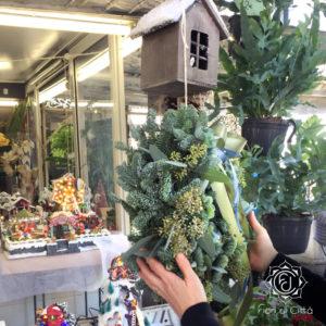 Una ghirlanda natalizia realizzata con rami di pino argentato e fiori di Hydrangea, ortensia.