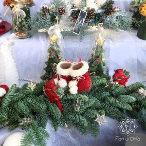 centrotavola natalizio con rami di pino e scarpette rosse e bianche in panno